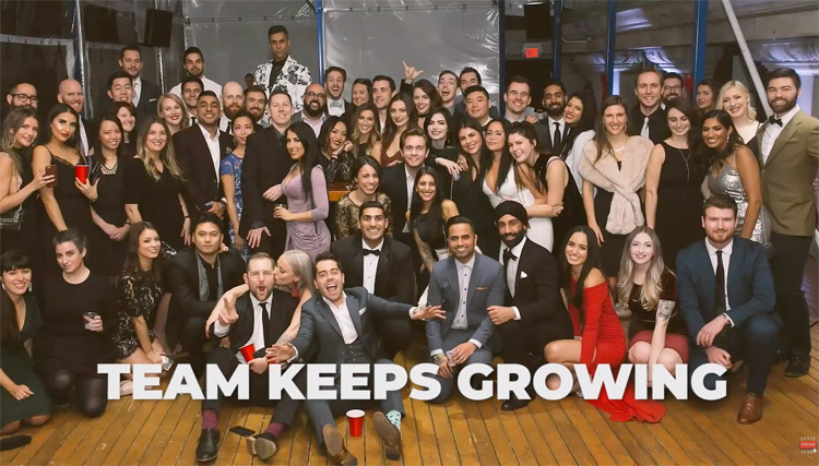 "A group photo of a few dozen people in formal wear with the words ""TEAM KEEPS GROWING"" superimposed."