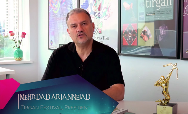 Mehrdad Ariannejad, as seen in a promotional video for the Tirgan Festival. He's sitting in an office with past festival posted on the wall an a statuette of a golden archer on his desk.