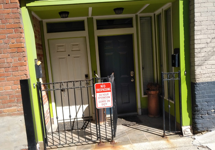 "Two doors in an alcove framed by a neon green lintel. In front is a low-rising gate, to which is affixed a sign: ""NO TRESPASSING – 24-Hour Operation – Guard on Duty"""