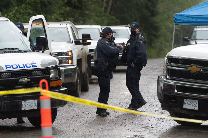 Two RCMP officers, a man and a woman, on a dirt road lined with police vehicles on each side. In the foreground is yellow police tape.
