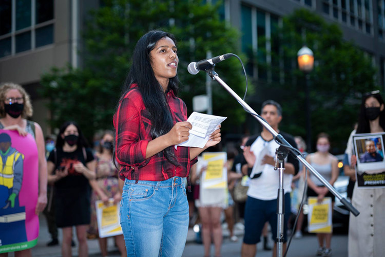 A young woman in a plaid red shirt and jeans speaks into a microphone set up on a street. Behind her are a row of people holding placards.